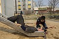 U.S. Navy Religious Program Specialist 3rd Class Jacob Birtola, with the III Marine Expeditionary Forces Headquarters Group, gets pulled down a slide by a South Korean elementary School student March 27, 2014 140327-M-UQ794-164.jpg