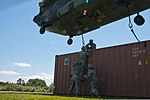 U.S. Soldiers of the 390th Seaport Operations Company (SPOC) finish securing a sling-loaded shipping container to a CH-47 Chinook helicopter during joint-service SPOC 13-2 training exercise at Joint Base 130804-A-GT254-014.jpg