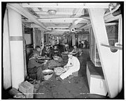 Crewmen peeling potatoes in the galley in preparation for a meal.
