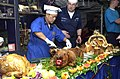 US Navy 021224-N-4142G-009 Master Chief Mess Management Specialist Arsenio Villanueva prepares cooked pig for Christmas dinner.jpg