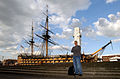US Navy 030507-N-4953E-032 Photographer's Mate 1st Class Michael Pendergrass poses for a photo in front of the worlds oldest commissioned ship, the HMS Victory, home ported in Portsmouth, England.jpg