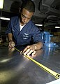 US Navy 041118-N-0246T-013 Aviation Structural Mechanic Airman Christopher Nettles of Delhi, La., measures sheet metal for a quality-of-life project in the Aircraft Intermediate Maintenance Department (AIMD) metal shop aboard.jpg