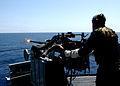 US Navy 050505-N-8146B-005 Gunner's Mate Seaman Gabino Martinez fires a MK-38 25mm machine gun system during a training exercise aboard the amphibious assault ship USS Boxer (LHD 4).jpg