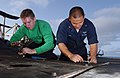 US Navy 060527-N-7730P-052 Aviation Support Equipment Technician 2nd Class Ronino Eva, and Aviation Support Equipment Technician Airman Robert Connor perform routine maintenance on a tractor on the flight deck during a no fly d.jpg