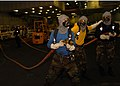 US Navy 061104-N-9723W-019 Hose team members move in to fight a simulated hangar bay fire during a general quarters drill.jpg