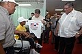 US Navy 070705-N-0194K-125 Ambassador William Eaton, U.S. ambassador to Panama, a child and his father with t-shirts as Camilo Alleyne, minister of health for Panama looks on aboard the Military Sealift Command hospital ship US.jpg