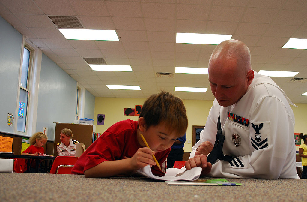 US Navy 090527-N-7375S-012 Petty Officer 2nd Class Jeff Kline, assigned to Navy Operational Support Center Rochester, helps a child with homework at the Cameron Community Ministries after school program during Rochester Navy We.jpg
