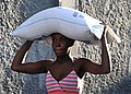 US Navy 100131-N-6214F-026 A women carries a 55-pound bag of rice distributed by the World Health Organization at a food distribution site in Port-au-Prince, Haiti.jpg