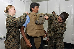 Body armor - United States Marines in July 2010 assist a Sri Lankan Navy sailor in trying on a Modular Tactical Vest.