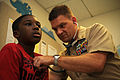 US Navy 110317-N-YR391-002 Senior Chief Hospital Corpsman Michael Holmes, assigned to Naval Hospital Jacksonville, examines a boy as part of an on.jpg
