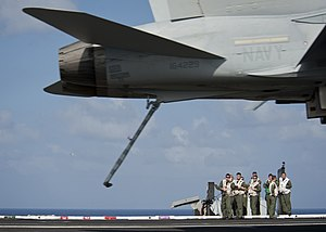 US Navy 111222-N-DR144-395 Landing signal officers supervise the arrested recovery of an F-A-18C Hornet on the flight deck aboard the Nimitz-class.jpg