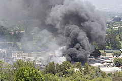 A large plume of gray smoke rises from a complex of buildings in a wooded area, seen from slightly above