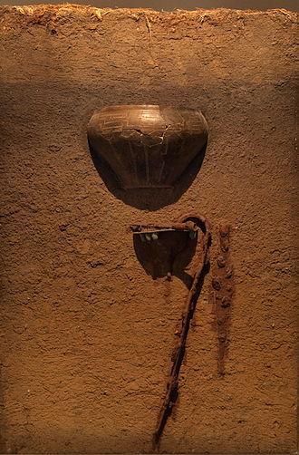 Grave goods - Model of the warrior's burial 'Hamburg-Marmstorf Grave No. 216', dating to circa 50 A.D., Hamburg-Marmstorf, Hamburg, Germany. At the upper edge are turf and the plough horizon. Below are the burial in a ceramic urn and beneath that the grave goods.