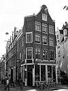 foto van Hoekhuis met klokgevel en gebeeldhouwde trapvensters
