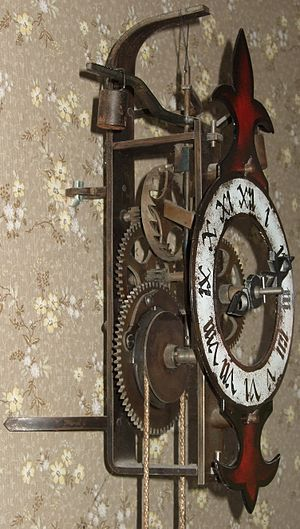 Verge escapement - Modern reproduction of an early verge and foliot clock.  The pointed-tooth verge wheel is visible, with the wooden foliot rod and suspended weight above it.