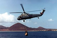 A helicopter flies over the water with a load slung below. In the background is an island with a series of pyramid-shaped peaks.