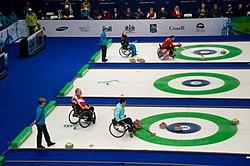 Duas partidas acontecem simultanemante. Na pista mais acima, um jogador lança uma pedra com a ajuda de um suporte semelhante a uma vara. Na pista de baixo, jogadores observam o posicionamento das pedras. Há uma pista vazia ao centro da imagem.