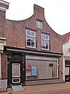 foto van Huis met ingezwenkte halsgevel zonder top en aanzetkrullen en met voordeur met pilasteromlijsting