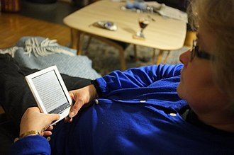E-book - A woman reading an e-book on an e-reader.