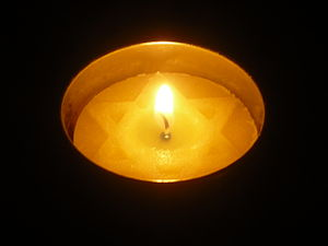 English: A lit Yom Hashoah candle in a dark ro...
