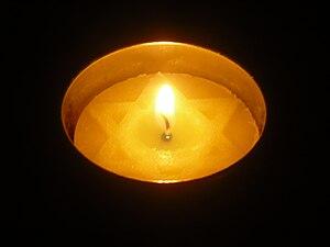 English: A lit Yom Hashoah candle in a dark ro...