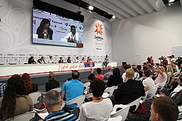 A press conference during the 2012 contest; the Serbian delegation are seated at a long table with rows of journalists seated facing them, with a large screen on the wall behind the delegation projecting a live relay of the conference.