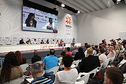 Una conferenza stampa durante il concorso 2012;  la delegazione serba è seduta a un lungo tavolo con file di giornalisti seduti di fronte a loro, con un grande schermo sul muro dietro la delegazione che proietta una staffetta in diretta della conferenza.