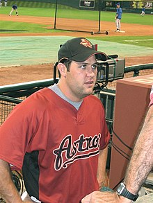 "A man in a red baseball jersey with ""ASTROS"" on the chest and black cap stands in a baseball dugout looking up."