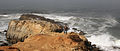 A fisherman is walking over rock formation at Pescadero State Beach.jpg
