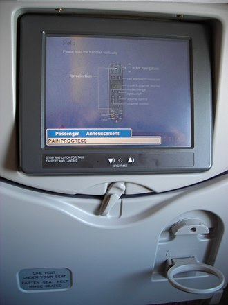 Airline seat - Control screen fixed to an economy class airline seat (Thai Airways International Airbus A340); the tray is stowed.