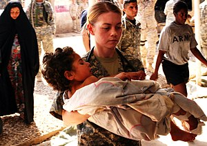 Casualties of the Iraq War - A soldier carries a wounded Iraqi child into the Charlie Medical Centre at Camp Ramadi, Iraq (March 20, 2007).
