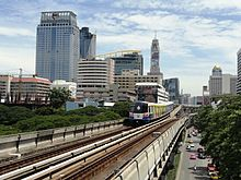 An elevated train, painted in blue, white and a red stripe and with advertisements, running above a road lined with many tall buildings and with many cars