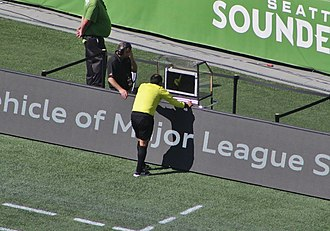 Video assistant referee - A Major League Soccer referee reviewing a play using a sideline monitor