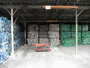 PET bottle recycling - Bales of crushed PET bottles sorted according to color: blue, transparent, and green.