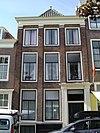 foto van Huis met pilastergevel op plint. Houten piron. Grote gecanneleerde voordeuromlijsting, gesneden deurkalf en geornamenteerde voordeur