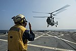 Boatswain's Mate 3rd Class Brittany Chiles directs INS Ranvijay's KV-28 Helix helicopter as it prepares to land on the flight deck of the USS McCampbell.jpg