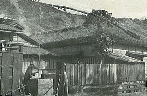 Bonin Islands - A man at a well, alongside buildings with the thatched roofs, weather-beaten unpainted sides and paper partitions and windows, characteristic of the islands before World War II