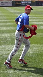 "A man in grey pants, a blue baseball jersey, and a red baseball cap with ""P"" on it jogs on a grass field while carrying a red article of clothing in his right hand."