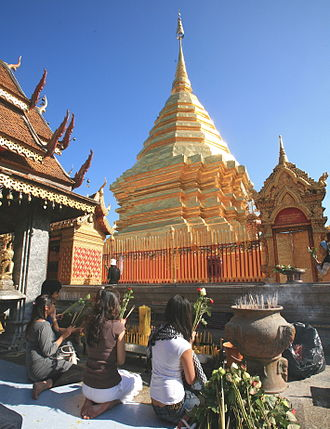 Offering (Buddhism) - Worshippers making offerings of incense, flowers and candles to a chedi at Wat Doi Suthep, Chiang Mai, Thailand