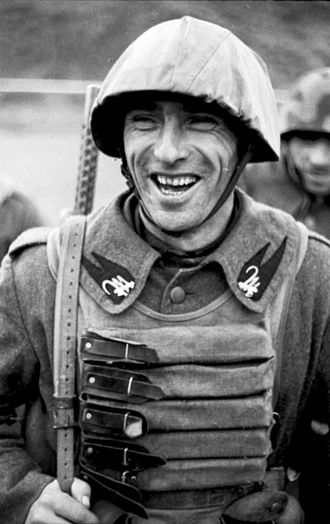 """Beretta Model 38 -  Soldier of an assault Battalion of the Republican National Guard (GNR) of Repubblica Sociale Italiana, armed with a MAB 38A and wearing a """"Samurai"""" magazine-holding vest."""