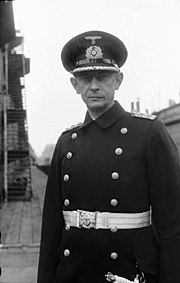 The head and upper torso of a man. He wears a peaked cap, black naval coat and a white belt with dagger. His facial expression is determined; his eyes are looking straight into the camera.