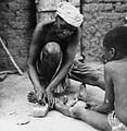 COLLECTIE TROPENMUSEUM Een lokale genezer behandelt een beenwond van een jongen TMnr 20010370.jpg