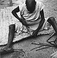 COLLECTIE TROPENMUSEUM Een man bezig met het omzomen van een uit riet gevochten slaapmat TMnr 20010536.jpg