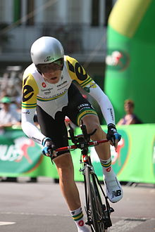 A road racing cyclist wearing a predominantly white and black skinsuit with green and gold trim.