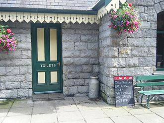 Castletown railway station - Detail of the building with period milk churn and blackboards