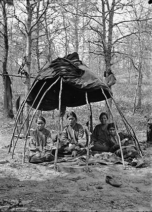 Truman Lowe - Four Winnebago women under a structure commonly seen as an influence in Lowe's work, from the Wisconsin Historical Society