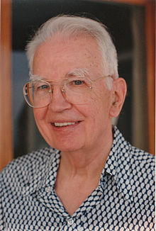 Coase looking to the camera and smiling, wearing a suit and tie