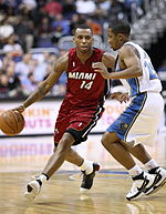 A basketball player, wearing a red jersey with the word «MIAMI» and the number 14 in the front, is dribbling the basketball while another basketball player, wearing a white jersey, attempts to defend him.