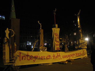 "Swiss minaret referendum, 2009 - On the evening of the vote, demonstrations against the result were held in Switzerland's major cities. The banner beneath the makeshift minarets reads: ""Integrate rather than exclude."""