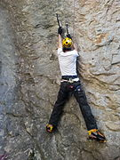Un grimpeur progressant en dry-tooling sur une paroi rocheuse